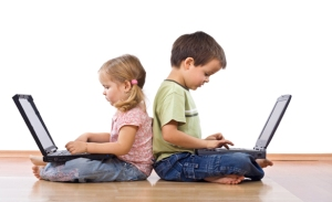 Siblings using laptops